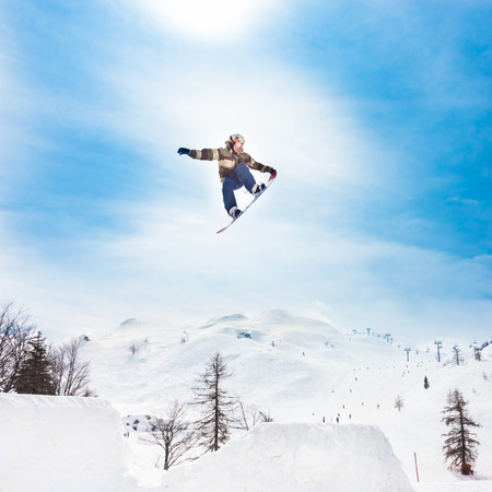 Free style snowboarder performing a high up in the sky nose grab jump. Snow covered mountains in the background. photo