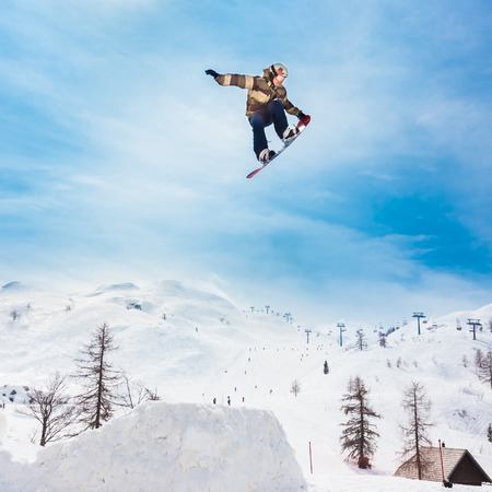 spectacular: Free style snowboarder performing a high up in the sky nose grab jump. Snow covered mountains in the background. Stock Photo