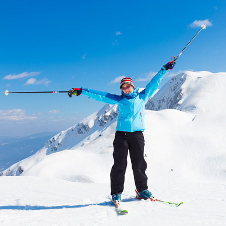 Excited woman skier, hands rised in the Alps Mountains, Triglav natural park, Vogel, Slovenia. photo