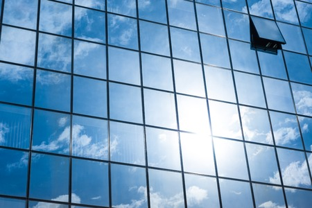sky reflection: Modern facade of glass and steel with open window reflecting sky and clouds.