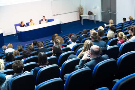 educator: Business Conference and Presentation. Audience at the conference hall. Stock Photo