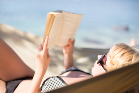 pleasure of reading: Beautiful girl lies on hammock on the beach and reads the book.