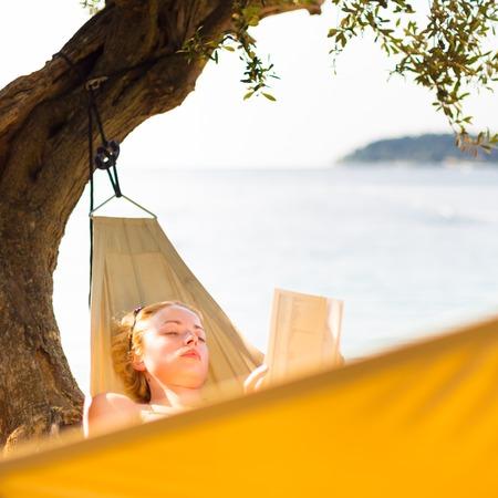 pleasure of reading: Beautiful girl lies on hammock on the beach reading book. Stock Photo