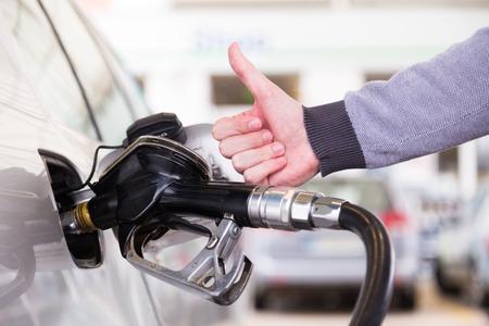 Benzine of benzine wordt gepompt in een motorvoertuig auto. Close-up van de mens, met duim omhoog gebaar, pompen benzine in de auto bij benzinestation. Stockfoto - 27987453
