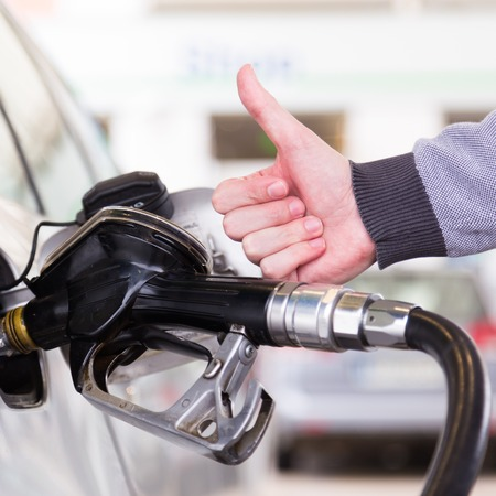 refuel: Petrol or gasoline being pumped into a motor vehicle car. Closeup of man, showing thumb up gesture, pumping gasoline fuel in car at gas station.
