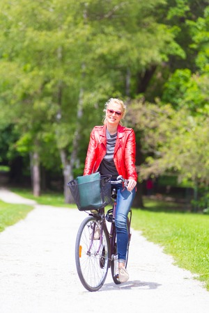 Happy young woman riding a bicycle in the park. photo