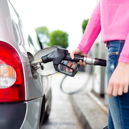 refuel: Closeup of woman pumping gasoline fuel in car at gas station. Petrol or gasoline being pumped into a motor vehicle car. Stock Photo