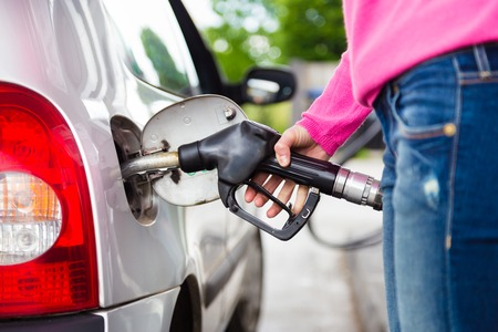 Closeup of woman pumping gasoline fuel in car at gas station. Petrol or gasoline being pumped into a motor vehicle car. Stock Photo