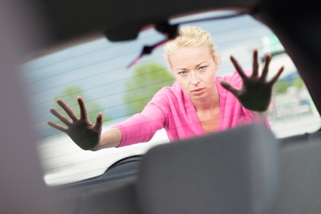 stuck: young woman pushing a car Stock Photo
