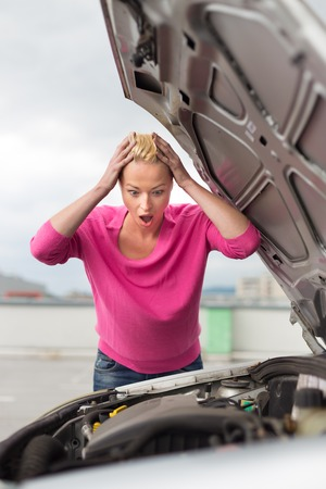 Stressed Young Woman with Car Defect  Engine breakdown  photo