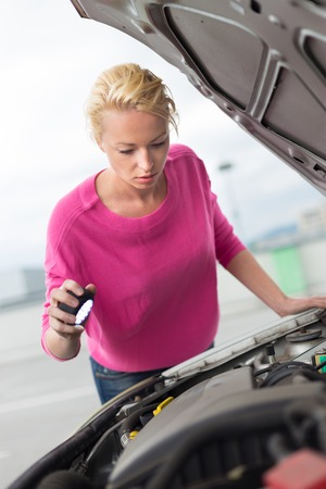 Self-sufficient confident modern young woman inspecting broken car engine with a flashlight in her hand. photo