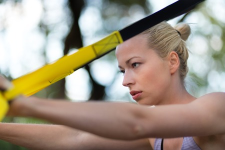 jungle gym: Young attractive woman does suspension training with fitness straps outdoors in the nature. Stock Photo