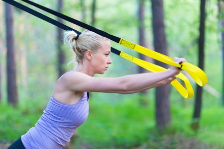 jungle gyms: Young attractive woman does suspension training with fitness straps outdoors in the nature. Stock Photo
