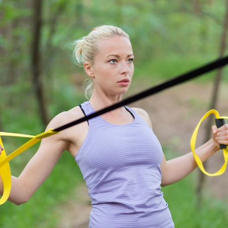 jungle gyms: Young attractive woman does suspension training with fitness straps outdoors in the nature
