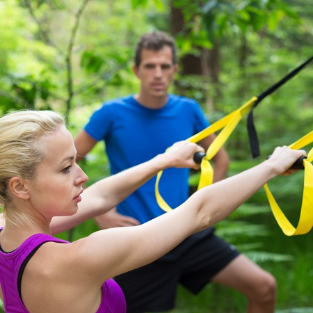 straps: Young active people does suspension training with fitness straps outdoors in the nature.