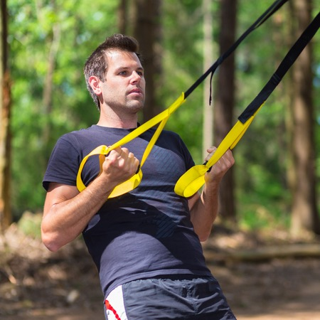 jungle gyms: Young attractiveman does suspension training with fitness straps outdoors in the nature. Stock Photo