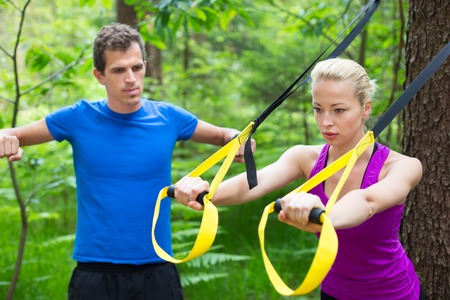 Young active people does suspension training with fitness straps outdoors in the nature. photo