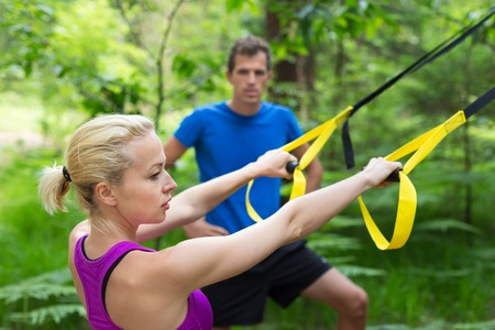 jungle gyms: Young active people does suspension training with fitness straps outdoors in the nature.