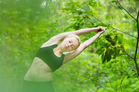 half: Young caucasian lady is practicing half moon yoga pose in the nature.