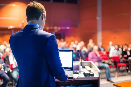 ビジネス会議やプレゼンテーションでスピーカー。会議ホールで聴衆。