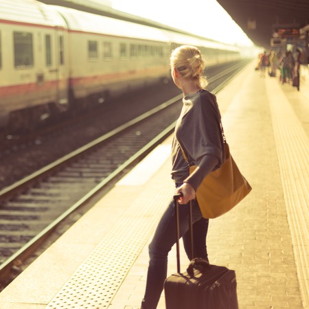 travelers: Blonde caucasian woman waiting at the railway station with a suitcase