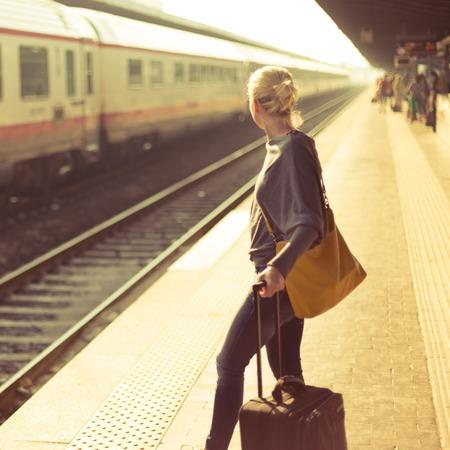 femme valise: Femme caucasien d'attente à la gare avec une valise