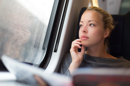 metro train: Thoughtful young lady reading while traveling by train
