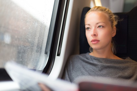 commuter train: Thoughtful young lady reading while traveling by train