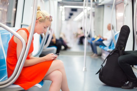 work station: Beautiful blonde caucasian lady in red dress traveling by metro