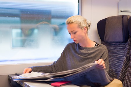 Thoughtful young lady reading while traveling by train  photo