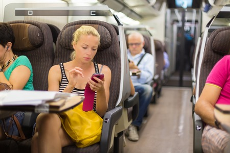 viagem: Senhora nova pensativa surfing on-line no smartphone durante a viagem de comboio