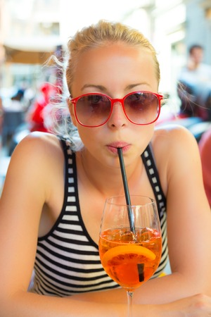 terracing: Woman terracing with aperol spritz cocktail in street cafe  Stock Photo