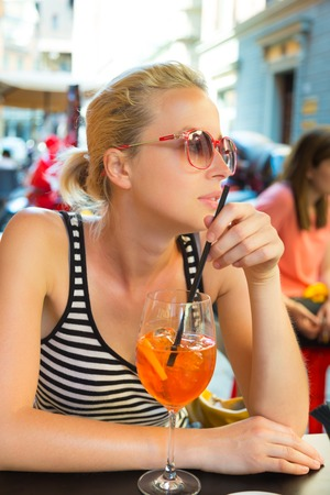 Woman terracing with aperol spritz cocktail in street cafe watching people walking by  Stock Photo