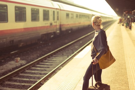 estacion de tren: Mujer caucásica rubia de espera en la estación de tren con una maleta Foto de archivo