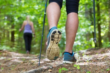 parejas caminando: Jóvenes aptos par de caminata en la naturaleza aventura, el deporte y el ejercicio Detalle del paso masculinos, las piernas y los bastones de marcha nórdica en maderas verdes