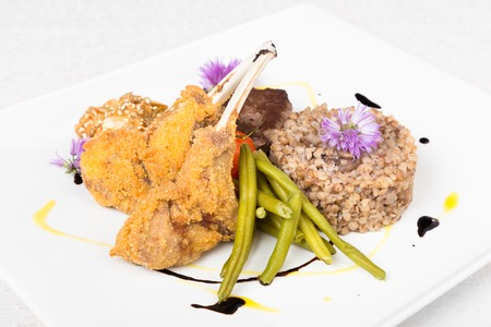 Mixed meat dish with green beans and buckwheat porridge with mushroomson white decorated plate  photo