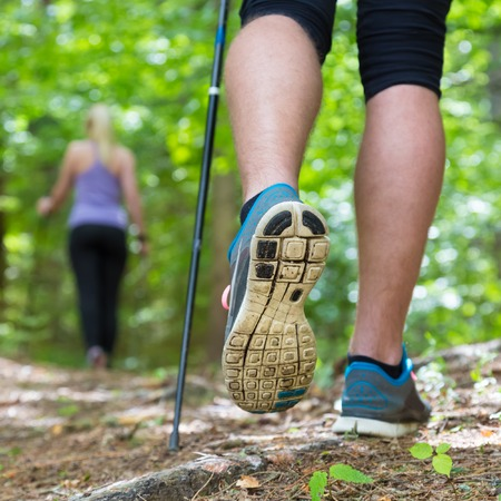 motion: Yngre passform par vandring i naturen äventyr, sport och motion Detalj av manliga steg, ben och gångstavar i gröna skogar