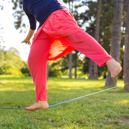 tightrope: Slacklining is a practice in balance that typically uses nylon or polyester webbing tensioned between two anchor points