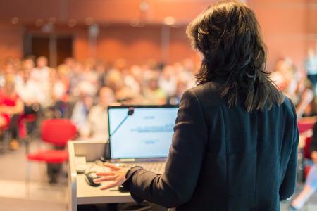 Obchodní žena přednášel na konferenci publikum na přednáškovém sále Reklamní fotografie