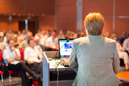 professor: Senior business woman lecturing at Conference  Audience at the lecture hall  Stock Photo