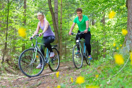 Young spoty active cople biking in nature Active lifestyle\ Activities and recreation outdoors