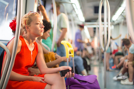 Beautiful blonde caucasian lady in red dress traveling by metro  photo