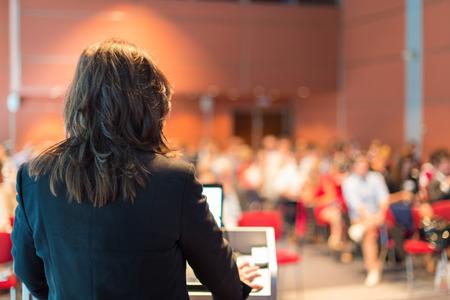 akademický: Obchodní žena přednášel na konferenci publikum na přednáškovém sále Reklamní fotografie