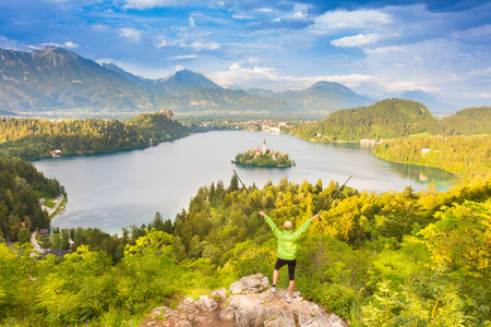 bled: Made it  Young spoty active lady with hiking sticks and hands rised admiring beautiful nature around Bled Lake in Julian Alps, Slovenia