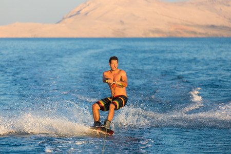 Wakeboarder in colorful shorts riding in sunset  Stock Photo
