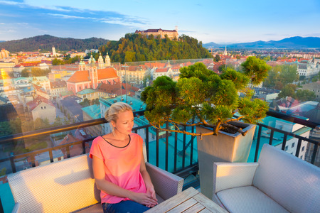 ljubljana: Female tourist enjoying in rooftop bar with panoramic view of Slovenian capital Ljubljana at sunset