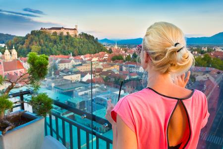 ljubljana: Female tourist enjoying panoramic view of Slovenian capital Ljubljana at sunset