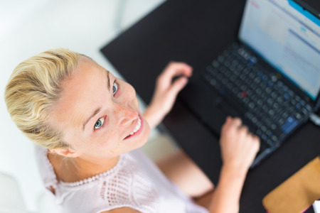 Cheerful relaxed business woman typing on a laptop computer photo
