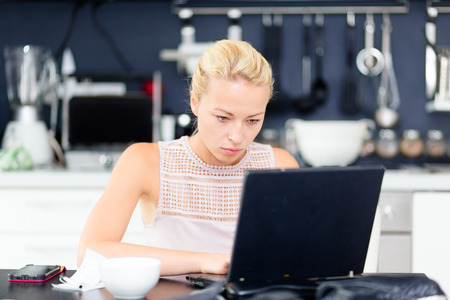 Business woman working remotely from her dining table photo