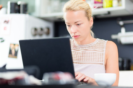 Business woman working remotly from her dining table  Home kitchen in the background  photo